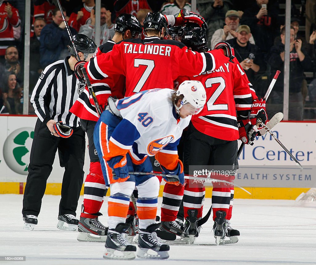 Henrik Tallinder #7 of the New Jersey Devils is congratulated by his teammates after scoring a goal as Michael Grabner #40 of the New York Islanders skates away during the game at the Prudential Center on January 31, 2013 in Newark, New Jersey.