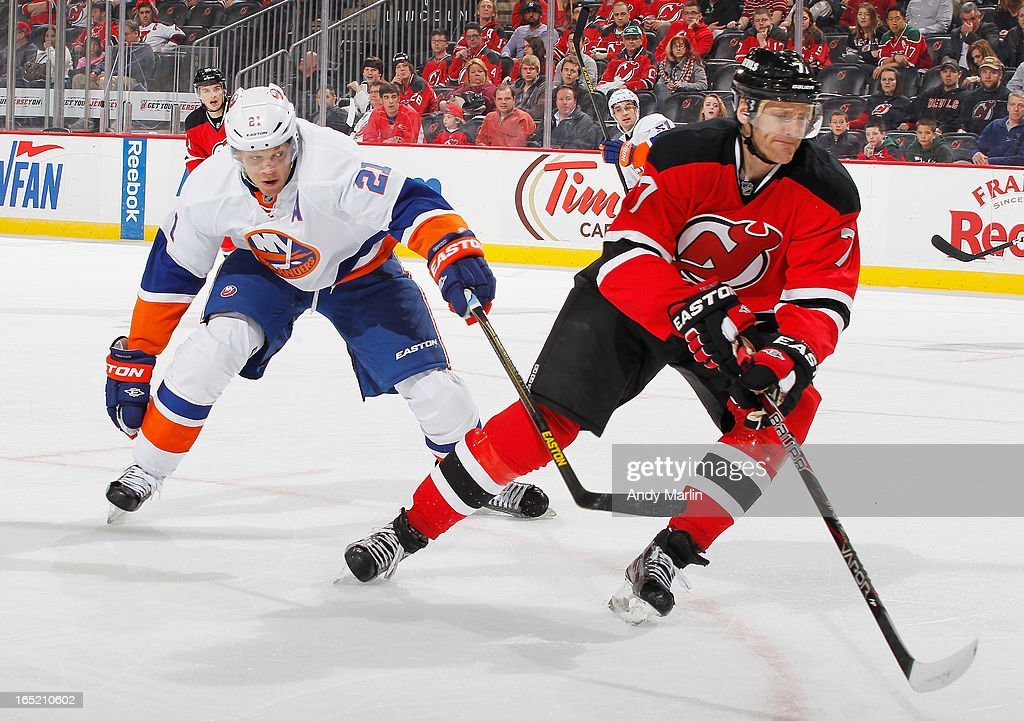 <a gi-track='captionPersonalityLinkClicked' href=/galleries/search?phrase=Henrik+Tallinder&family=editorial&specificpeople=204661 ng-click='$event.stopPropagation()'>Henrik Tallinder</a> #7 of the New Jersey Devils knocks the puck away while being pursued by <a gi-track='captionPersonalityLinkClicked' href=/galleries/search?phrase=Kyle+Okposo&family=editorial&specificpeople=540469 ng-click='$event.stopPropagation()'>Kyle Okposo</a> #21 of the New York Islanders during the game at the Prudential Center on April 1, 2013 in Newark, New Jersey.