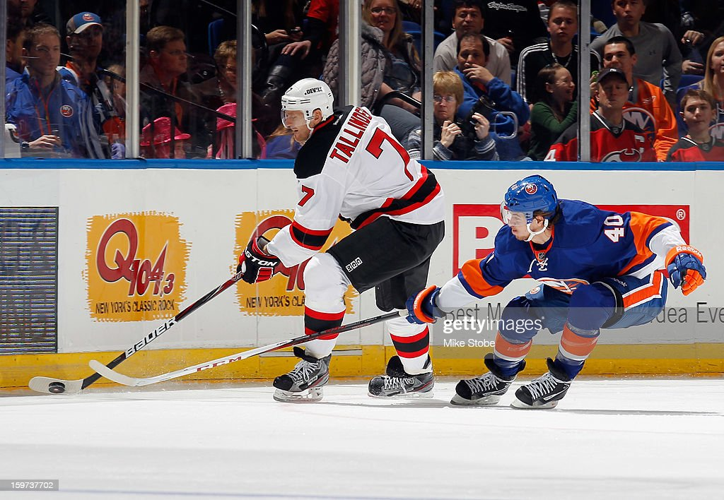 Henrik Tallinder #7 of the New Jersey Devils protects the puck as Michael Grabner #40 of the New York Islanders pursues him at Nassau Veterans Memorial Coliseum on January 19, 2013 in Uniondale, New York. The Devils defeated the Islanders 2-1.