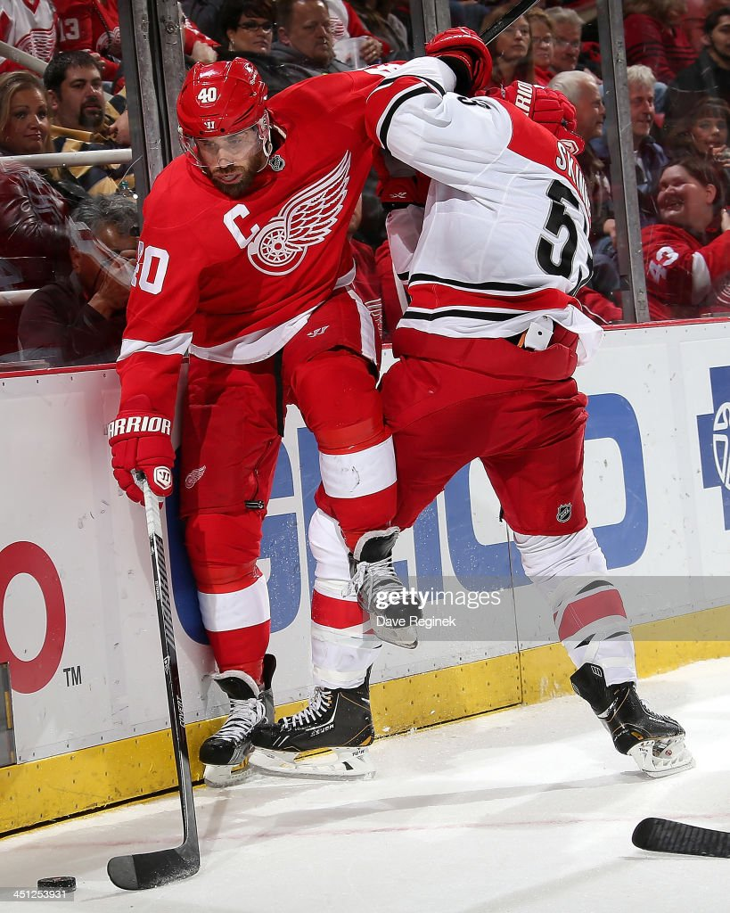 <a gi-track='captionPersonalityLinkClicked' href=/galleries/search?phrase=Henrik+Zetterberg&family=editorial&specificpeople=201520 ng-click='$event.stopPropagation()'>Henrik Zetterberg</a> #40 of the Detroit Red Wings barely misses a big hit from <a gi-track='captionPersonalityLinkClicked' href=/galleries/search?phrase=Jeff+Skinner&family=editorial&specificpeople=3147596 ng-click='$event.stopPropagation()'>Jeff Skinner</a> #53 of the Carolina Hurricanes during an NHL game at Joe Louis Arena on November 21, 2013 in Detroit, Michigan. Detroit defeated Carolina 4-3