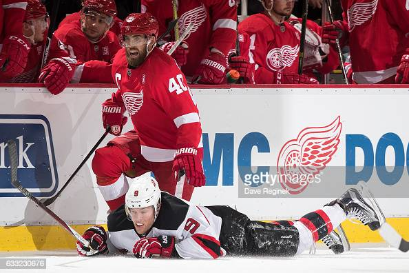 Henrik Zetterberg of the Detroit Red Wings battles along the boards with Taylor Hall of the New Jersey Devils during an NHL game at Joe Louis Arena...