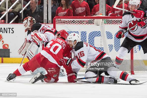 Henrik Zetterberg of the Detroit Red Wings battles for position in front of the net with Jacob Josefson of the New Jersey Devils as Cory Schneider of...