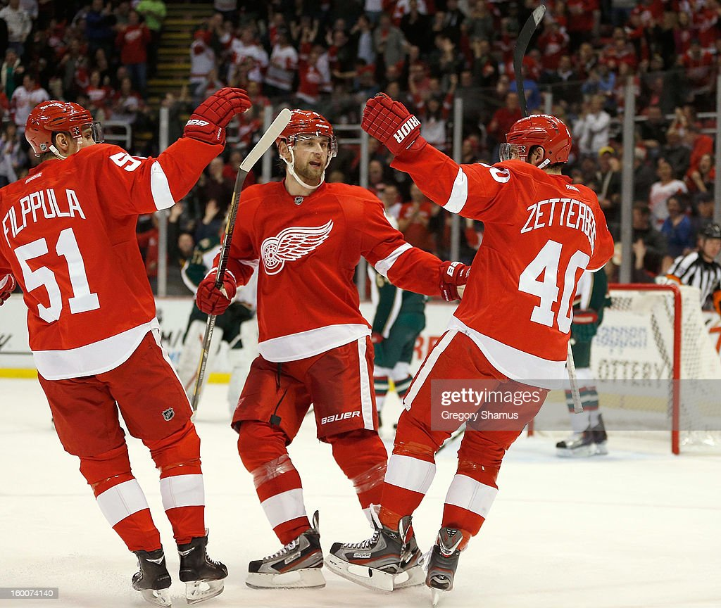 <a gi-track='captionPersonalityLinkClicked' href=/galleries/search?phrase=Henrik+Zetterberg&family=editorial&specificpeople=201520 ng-click='$event.stopPropagation()'>Henrik Zetterberg</a> #40 of the Detroit Red Wings celebrates a second period goal with <a gi-track='captionPersonalityLinkClicked' href=/galleries/search?phrase=Jakub+Kindl&family=editorial&specificpeople=716743 ng-click='$event.stopPropagation()'>Jakub Kindl</a> #4 and <a gi-track='captionPersonalityLinkClicked' href=/galleries/search?phrase=Valtteri+Filppula&family=editorial&specificpeople=2234404 ng-click='$event.stopPropagation()'>Valtteri Filppula</a> #51while playing the Minnesota Wild at Joe Louis Arena on January 25, 2013 in Detroit, Michigan. Detroit won the game 5-3.