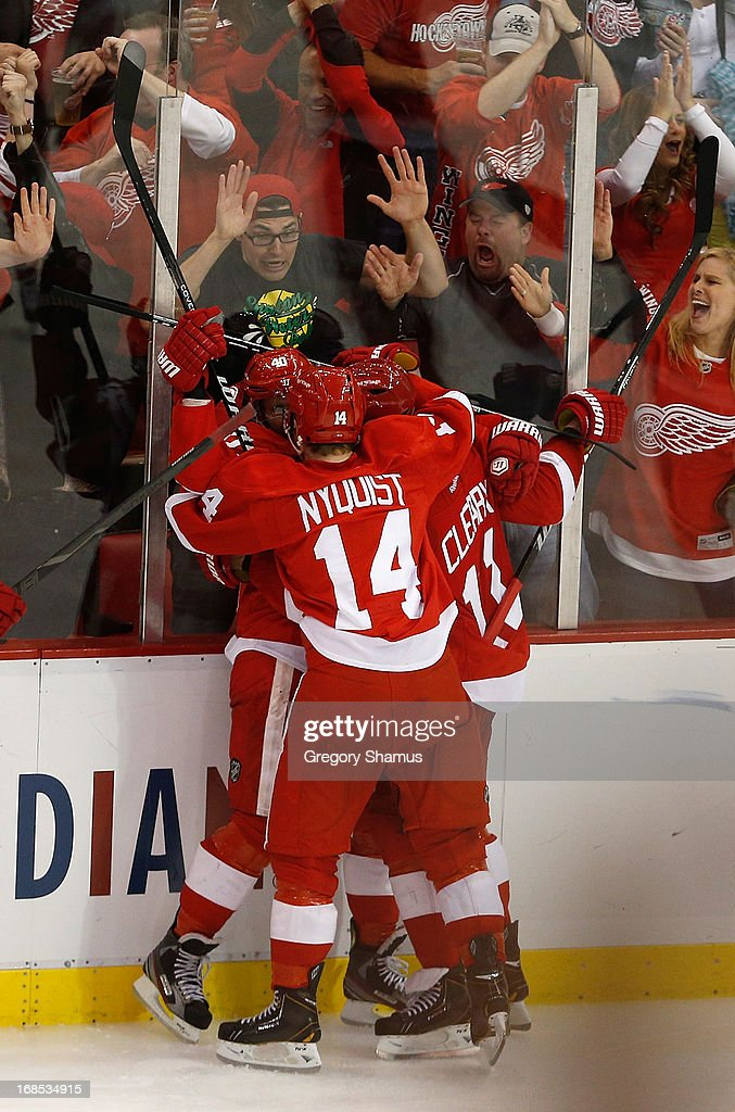<a gi-track='captionPersonalityLinkClicked' href=/galleries/search?phrase=Henrik+Zetterberg&family=editorial&specificpeople=201520 ng-click='$event.stopPropagation()'>Henrik Zetterberg</a> #40 of the Detroit Red Wings celebrates his overtime goal to beat the Anaheim Ducks 4-3 with teammates <a gi-track='captionPersonalityLinkClicked' href=/galleries/search?phrase=Gustav+Nyquist&family=editorial&specificpeople=5491209 ng-click='$event.stopPropagation()'>Gustav Nyquist</a> #14 and <a gi-track='captionPersonalityLinkClicked' href=/galleries/search?phrase=Daniel+Cleary&family=editorial&specificpeople=220490 ng-click='$event.stopPropagation()'>Daniel Cleary</a> #11 in Game Six of the Western Conference Quarterfinals during the 2013 NHL Stanley Cup Playoffs at Joe Louis Arena on May 10, 2013 in Detroit, Michigan. The series is tied 3-3.