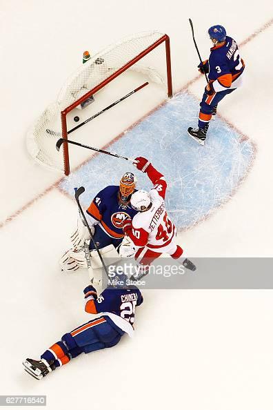 Henrik Zetterberg of the Detroit Red Wings celebrates teamates Danny DeKeyser game winning overtime goal as Jaroslav Halak of the New York Islanders...