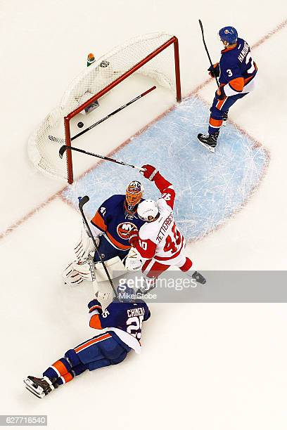 Henrik Zetterberg of the Detroit Red Wings celebrates teamates Danny DeKeyser game winning overtime goal as Jaroslav Halak of the New York Islanders...