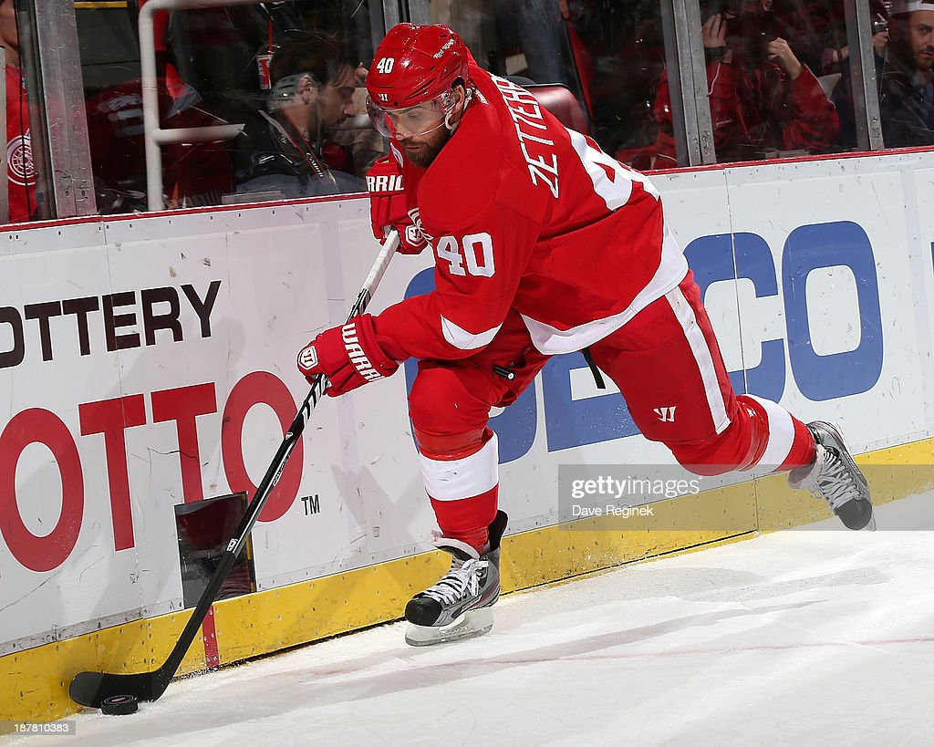 <a gi-track='captionPersonalityLinkClicked' href=/galleries/search?phrase=Henrik+Zetterberg&family=editorial&specificpeople=201520 ng-click='$event.stopPropagation()'>Henrik Zetterberg</a> #40 of the Detroit Red Wings dig the puck out of the corner during an NHL game against the Winnipeg Jets at Joe Louis Arena on November 12, 2013 in Detroit, Michigan.
