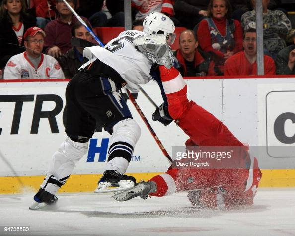 Henrik Zetterberg of the Detroit Red Wings falls to the ice as he gets checked by Mattias Ohlund of theTampa Bay Lightning during a NHL game at Joe...