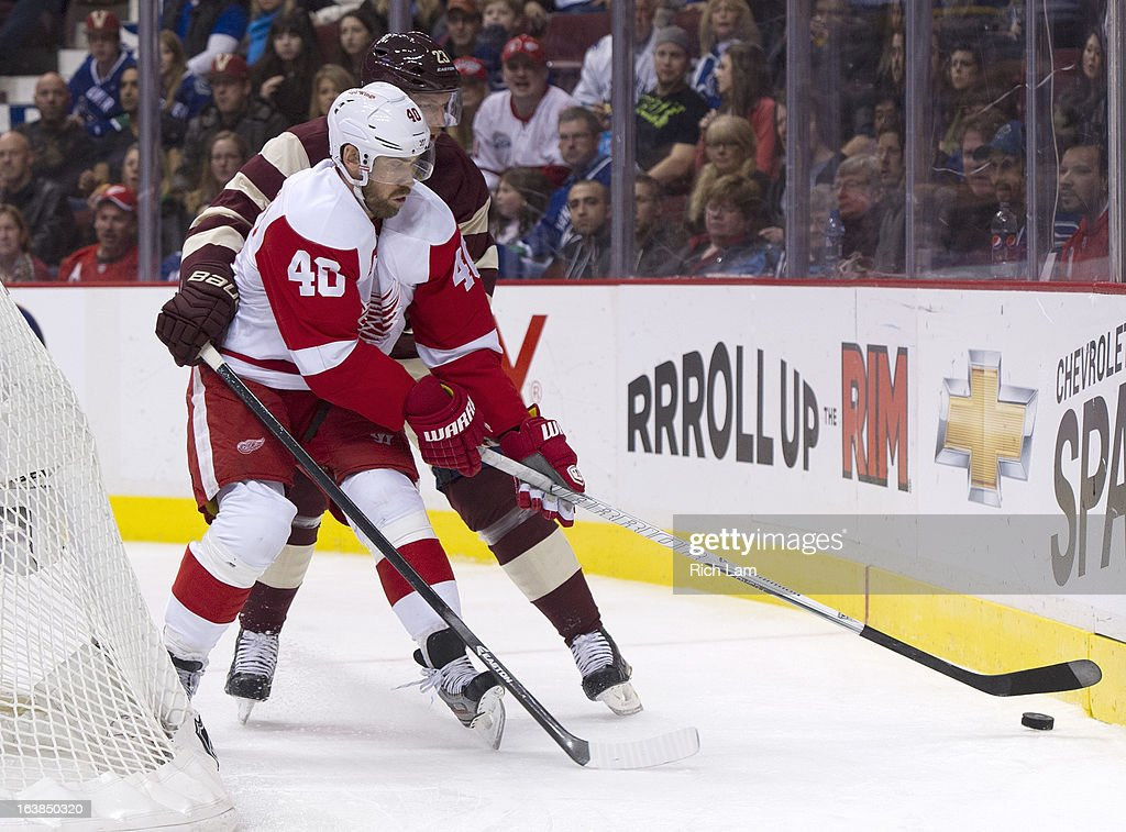 <a gi-track='captionPersonalityLinkClicked' href=/galleries/search?phrase=Henrik+Zetterberg&family=editorial&specificpeople=201520 ng-click='$event.stopPropagation()'>Henrik Zetterberg</a> #40 of the Detroit Red Wings gains control of the puck while being checked by <a gi-track='captionPersonalityLinkClicked' href=/galleries/search?phrase=Alexander+Edler&family=editorial&specificpeople=882987 ng-click='$event.stopPropagation()'>Alexander Edler</a> #23 of the Vancouver Canucks during the third period of NHL action on March 16, 2013 at Rogers Arena in Vancouver, British Columbia, Canada.