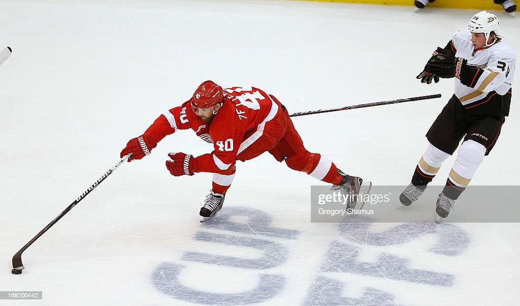 <a gi-track='captionPersonalityLinkClicked' href=/galleries/search?phrase=Henrik+Zetterberg&family=editorial&specificpeople=201520 ng-click='$event.stopPropagation()'>Henrik Zetterberg</a> #40 of the Detroit Red Wings goes for the puck in overtime and takes the stick of <a gi-track='captionPersonalityLinkClicked' href=/galleries/search?phrase=Matt+Beleskey&family=editorial&specificpeople=570471 ng-click='$event.stopPropagation()'>Matt Beleskey</a> #39 of the Anaheim Ducks with him in Game Four of the Western Conference Quarterfinals during the 2013 NHL Stanley Cup Playoffs at Joe Louis Arena on May 6, 2013 in Detroit, Michigan. Detroit won the game 3-2 in overtime to tie the series 2-2.
