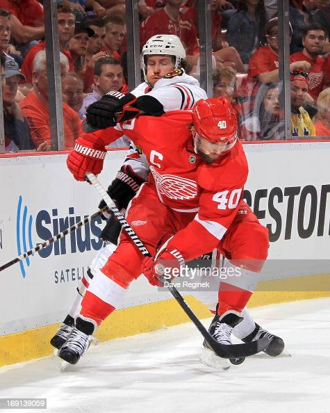 Henrik Zetterberg of the Detroit Red Wings handles the puck as Duncan Keith of the Chicago Blackhawks tries to defend him during Game Three of the...