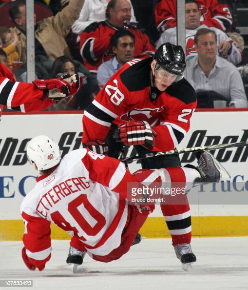 Henrik Zetterberg of the Detroit Red Wings is hit by Anton Volchenkov of the New Jersey Devils at the Prudential Center on December 11 2010 in Newark...