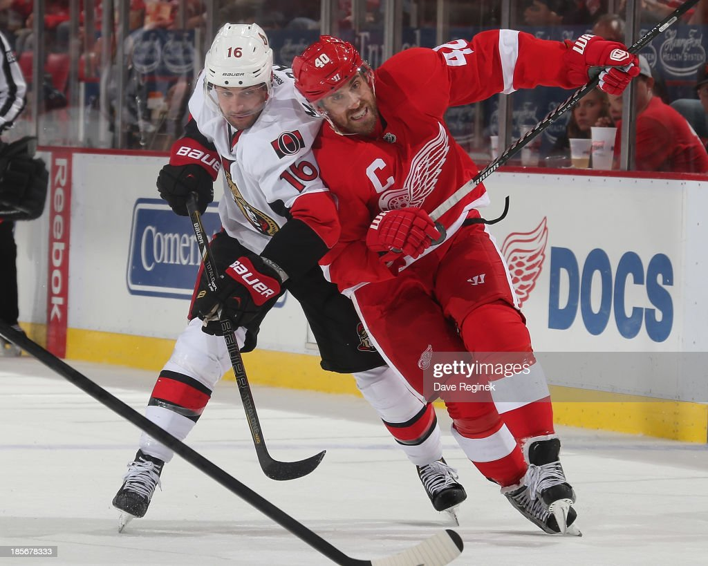 <a gi-track='captionPersonalityLinkClicked' href=/galleries/search?phrase=Henrik+Zetterberg&family=editorial&specificpeople=201520 ng-click='$event.stopPropagation()'>Henrik Zetterberg</a> #40 of the Detroit Red Wings is slowed up by <a gi-track='captionPersonalityLinkClicked' href=/galleries/search?phrase=Clarke+MacArthur&family=editorial&specificpeople=3949382 ng-click='$event.stopPropagation()'>Clarke MacArthur</a> #16 of the Ottawa Senators during an NHL game at Joe Louis Arena on October 23, 2013 in Detroit, Michigan. The Senators win 6-1