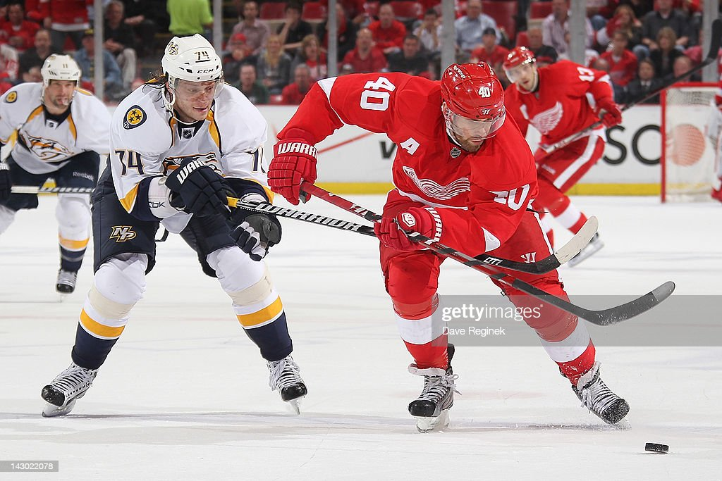 <a gi-track='captionPersonalityLinkClicked' href=/galleries/search?phrase=Henrik+Zetterberg&family=editorial&specificpeople=201520 ng-click='$event.stopPropagation()'>Henrik Zetterberg</a> #40 of the Detroit Red Wings moves the puck up ice as <a gi-track='captionPersonalityLinkClicked' href=/galleries/search?phrase=Sergei+Kostitsyn&family=editorial&specificpeople=599906 ng-click='$event.stopPropagation()'>Sergei Kostitsyn</a> #74 of the Nashville Predators battles after in Game Four of the Western Conference Quarterfinals during the 2012 NHL Stanley Cup Playoffs at Joe Louis Arena on April 17, 2012 in Detroit, Michigan. Nashville wins 3-1 and leads series 3-1.