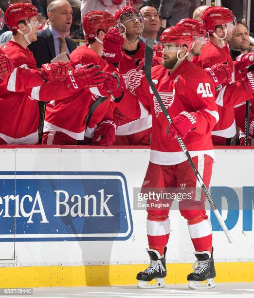 Henrik Zetterberg of the Detroit Red Wings pounds gloves with teammates on the bench following his second period goal during an NHL game against the...