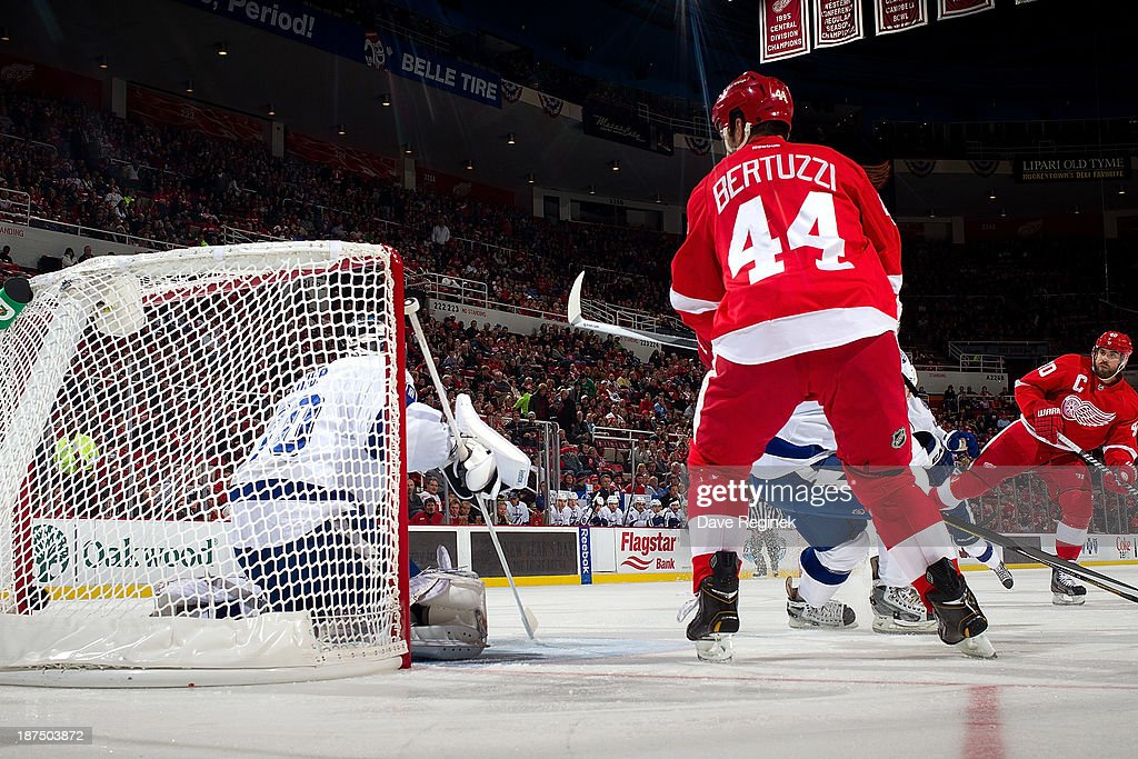 Henrik Zetterberg #40 of the Detroit Red Wings puts the puck in the back of the net against goalie Ben Bishop #30 of the Tampa Bay Lightning during an NHL game at Joe Louis Arena on November 9, 2013 in Detroit, Michigan.