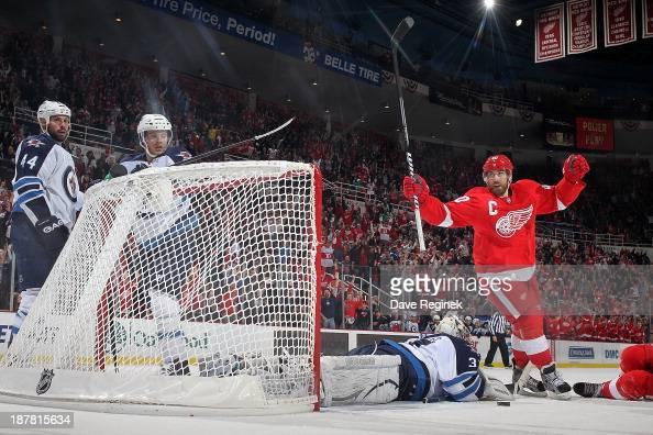 Henrik Zetterberg of the Detroit Red Wings raises his hands after teammate Pavel Datsyuk scores a goal while goalie Ondrej Pavelec of the Winnipeg...