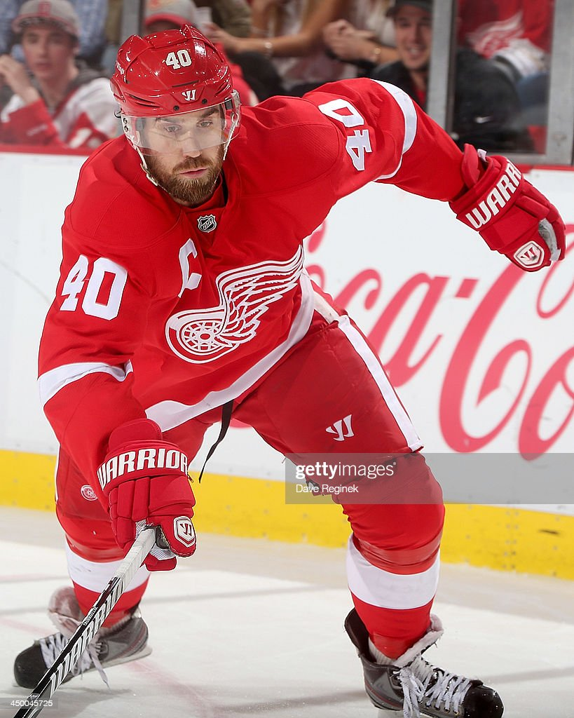 Henrik Zetterberg #40 of the Detroit Red Wings reaches after a loose puck during an NHL game against the Winnipeg Jets at Joe Louis Arena on November 12, 2013 in Detroit, Michigan. The Jets defeated Wings 3-2 in a shootout.