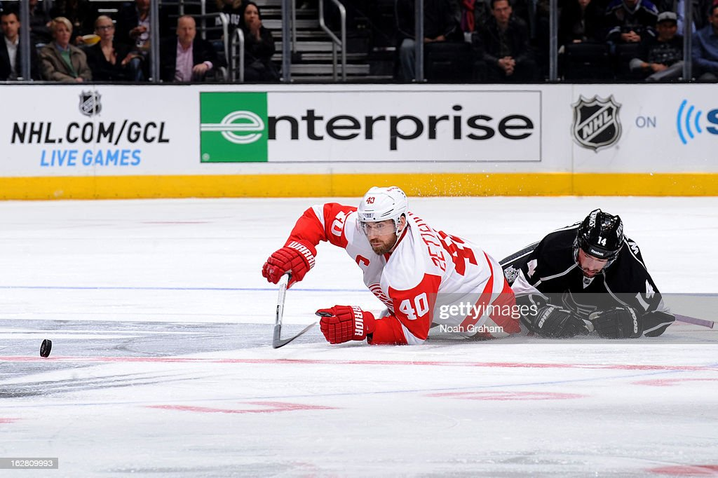 Henrik Zetterberg #40 of the Detroit Red Wings reaches for the puck against Justin Williams #14 of the Los Angeles Kings at Staples Center on February 27, 2013 in Los Angeles, California.