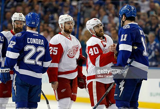 Henrik Zetterberg of the Detroit Red Wings shoes hands with Brian Boyle of the Tampa Bay Lightning as Mike Green waits following Game Five of the...