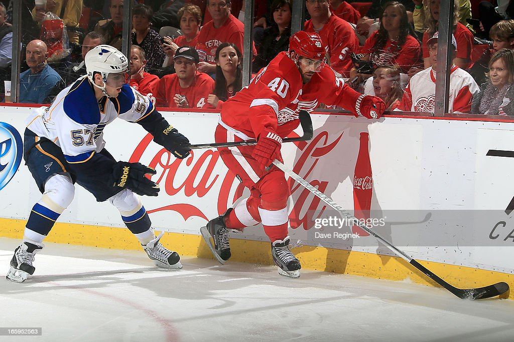 <a gi-track='captionPersonalityLinkClicked' href=/galleries/search?phrase=Henrik+Zetterberg&family=editorial&specificpeople=201520 ng-click='$event.stopPropagation()'>Henrik Zetterberg</a> #40 of the Detroit Red Wings skates with the puck as <a gi-track='captionPersonalityLinkClicked' href=/galleries/search?phrase=David+Perron&family=editorial&specificpeople=4282591 ng-click='$event.stopPropagation()'>David Perron</a> #57 of the St. Louis Blues puts a stick on him during a NHL game at Joe Louis Arena on April 7, 2013 in Detroit, Michigan. St. Louis defeated Detroit 1-0