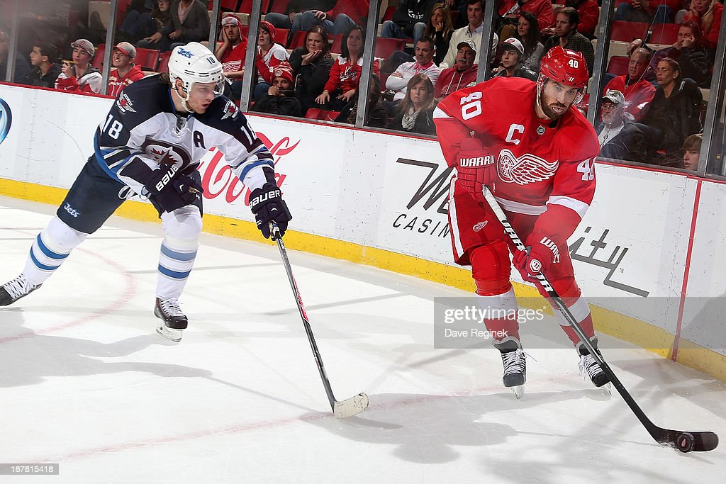 <a gi-track='captionPersonalityLinkClicked' href=/galleries/search?phrase=Henrik+Zetterberg&family=editorial&specificpeople=201520 ng-click='$event.stopPropagation()'>Henrik Zetterberg</a> #40 of the Detroit Red Wings skates with the puck as <a gi-track='captionPersonalityLinkClicked' href=/galleries/search?phrase=Bryan+Little&family=editorial&specificpeople=540533 ng-click='$event.stopPropagation()'>Bryan Little</a> #18 of the Winnipeg Jets defends him during an NHL game at Joe Louis Arena on November 12, 2013 in Detroit, Michigan. The Winnipeg Jets defeated the Detroit Red Wings 3-2 in a shootout