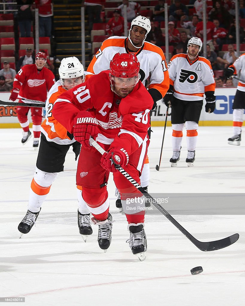 <a gi-track='captionPersonalityLinkClicked' href=/galleries/search?phrase=Henrik+Zetterberg&family=editorial&specificpeople=201520 ng-click='$event.stopPropagation()'>Henrik Zetterberg</a> #40 of the Detroit Red Wings slides in an empty net goal as <a gi-track='captionPersonalityLinkClicked' href=/galleries/search?phrase=Matt+Read&family=editorial&specificpeople=6783206 ng-click='$event.stopPropagation()'>Matt Read</a> #24 of the Philadelphia Flyers gives chase during a NHL game at Joe Louis Arena on October 12, 2013 in Detroit, Michigan. Detroit defeated Philadelphia 5-2.