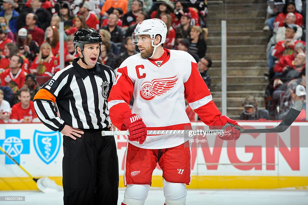 Henrik Zetterberg #40 of the Detroit Red Wings speaks with referee Brian Pochmara #16 during the NHL game against the Chicago Blackhawks on January 27, 2013 at the United Center in Chicago, Illinois.