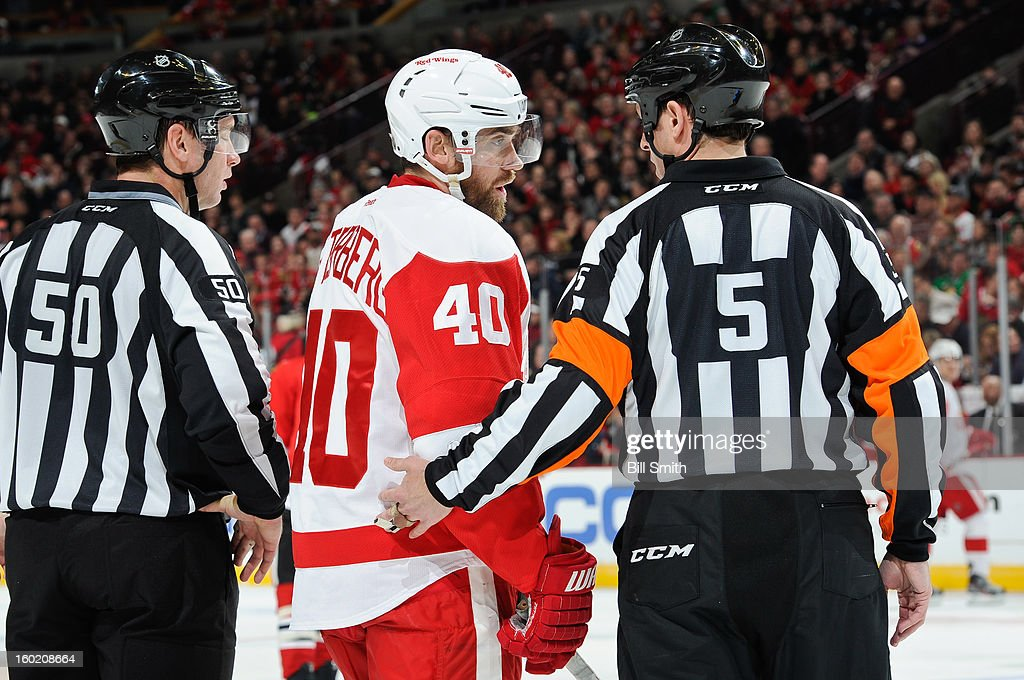 Henrik Zetterberg #44 of the Detroit Red Wings speaks with referee Chris Rooney #5 during the NHL game against the Chicago Blackhawks on January 27, 2013 at the United Center in Chicago, Illinois.
