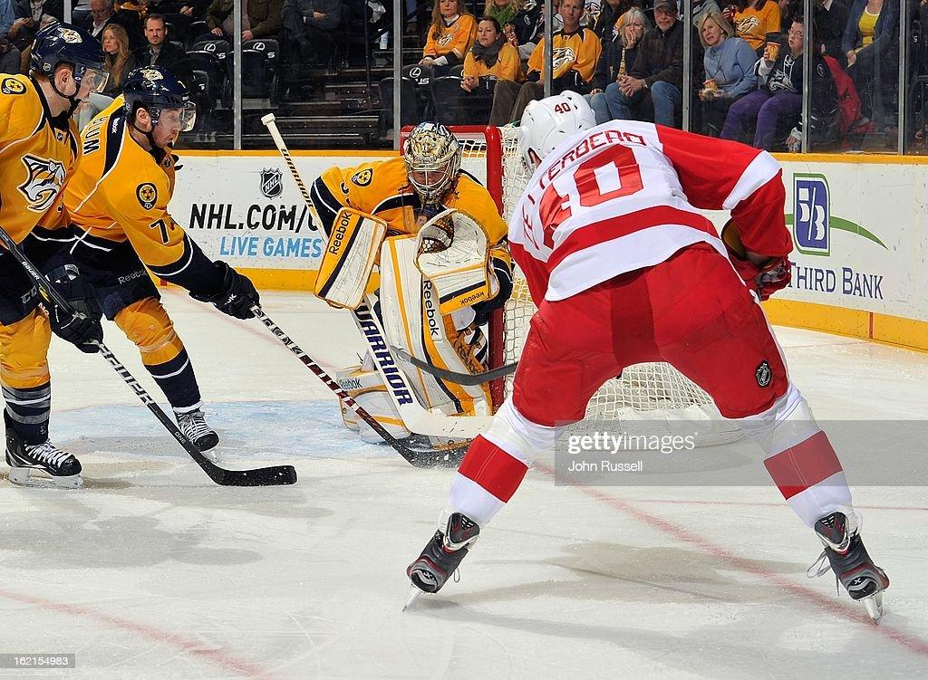 Henrik Zetterberg #40 of the Detroit Red Wings takes a shot on goalie Pekka Rinne #35 of the Nashville Predators at Bridgestone Arena on February 19, 2013 in Nashville, Tennessee.