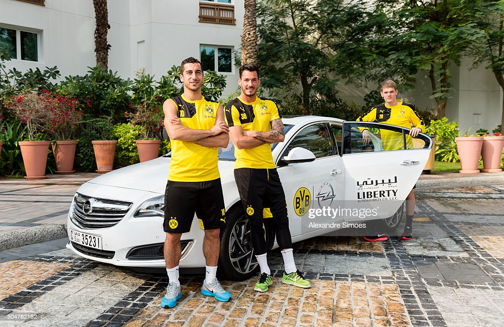 Henrikh Mkhitaryan goalkeeper Roman Buerki and Matthias Ginter posing infront of the team cars from Opel during Borussia Dortmund's training camp at...