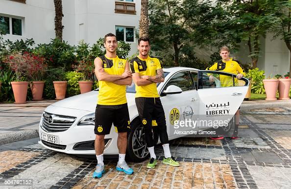 Henrikh Mkhitaryan goalkeeper Roman Buerki and Matthias Ginter posing infront of the team cars from Opel during Borussia Dortmund's training camp at...