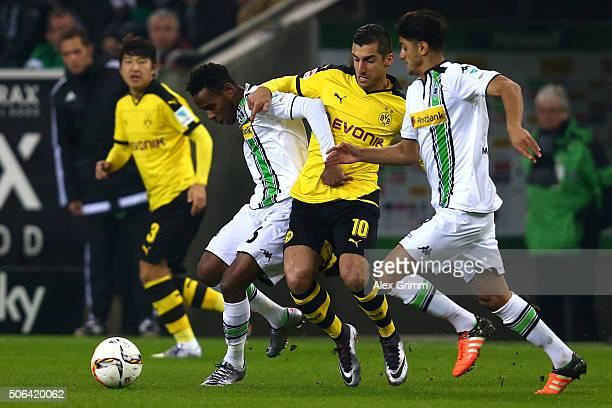 Henrikh Mkhitaryan of Borussia Dortmund battles with Ibrahima Traore and Mahmoud Dahoud of Borussia Moenchengladbach during the Bundesliga match...