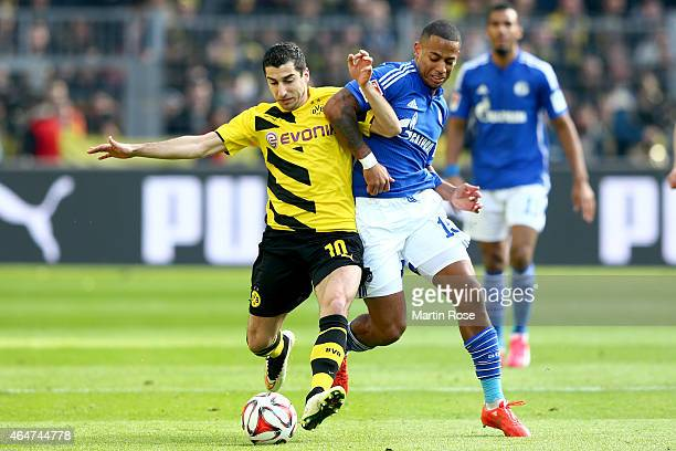 Henrikh Mkhitaryan of Dortmund battles for the ball with Dennis Aogo of Schalke during the Bundesliga match between Borussia Dortmund and FC Schalke...