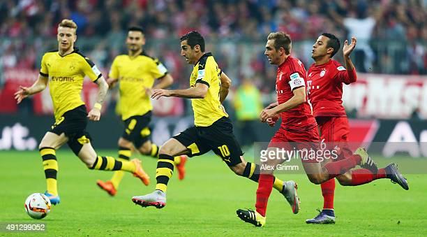 Henrikh Mkhitaryan of Dortmund eludes Philipp Lahm and Thiago Alcantara of Muenchen during the Bundesliga match between FC Bayern Muenchen and...