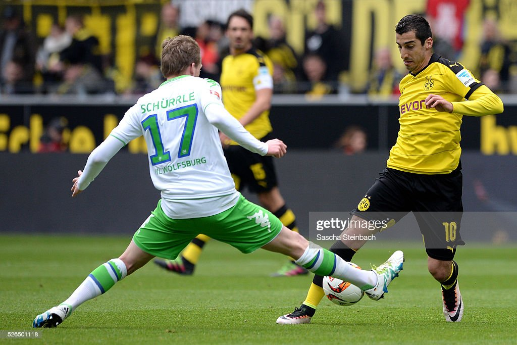 Henrikh Mkhitaryan (R) of Dortmund is challenged by Andre Schuerrle (L) of Wolfsburg during the Bundesliga match between Borussia Dortmund and VfL Wolfsburg at Signal Iduna Park on April 29, 2016 in Dortmund, Germany.