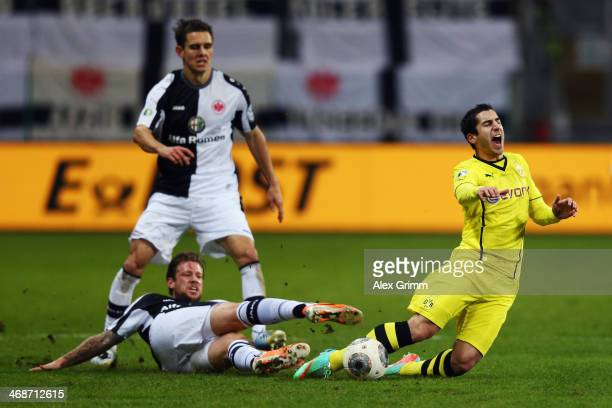 Henrikh Mkhitaryan of Dortmund is challenged by Marco Russ of Frankfurt during the DFB Cup quarterfinal match between Eintracht Frankfurt and...