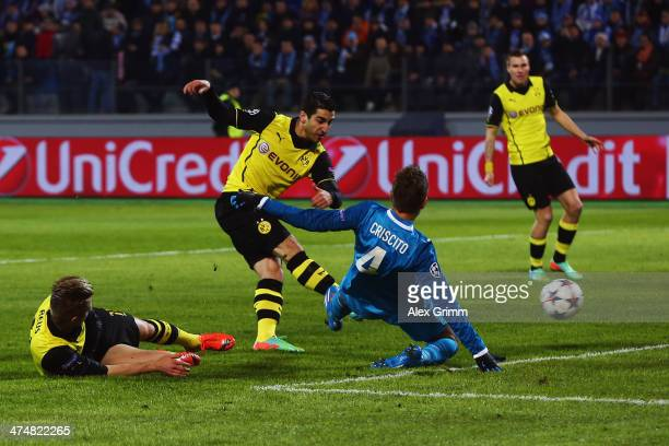 Henrikh Mkhitaryan of Dortmund scores his team's first goal against Domenico Criscito of Zenit during the UEFA Champions League Round of 16 match...