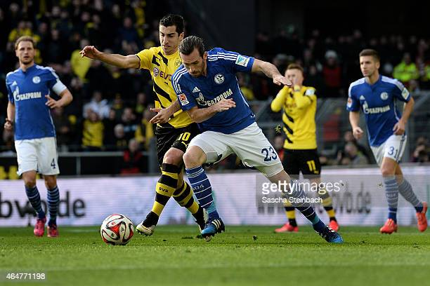 Henrikh Mkhitaryan of Dortmund vies with Christian Fuchs of Schalke during the Bundesliga match between Borussia Dortmund and FC Schalke 04 at Signal...