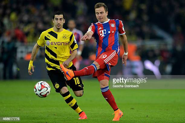 Henrikh Mkhitaryan of Dortmund vies with Mario Goetze of Muenchen during the Bundesliga match between Borussia Dortmund and FC Bayern Muenchen at...