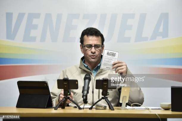 Henrique Capriles opposition leader and governor of the State of Miranda holds a voting card as he speaks during a press conference in Caracas...