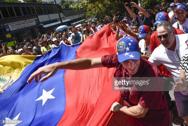 Henrique Capriles opposition leader and governor of the State of Miranda holds a large Venezuelan flag while making his way to a polling station...