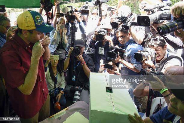 Henrique Capriles opposition leader and governor of the State of Miranda kisses a ballot before casting it at a polling station during a symbolic...