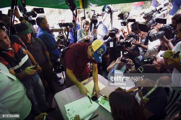 Henrique Capriles opposition leader and governor of the State of Miranda checks in at a polling station to vote during a symbolic Venezuelan...