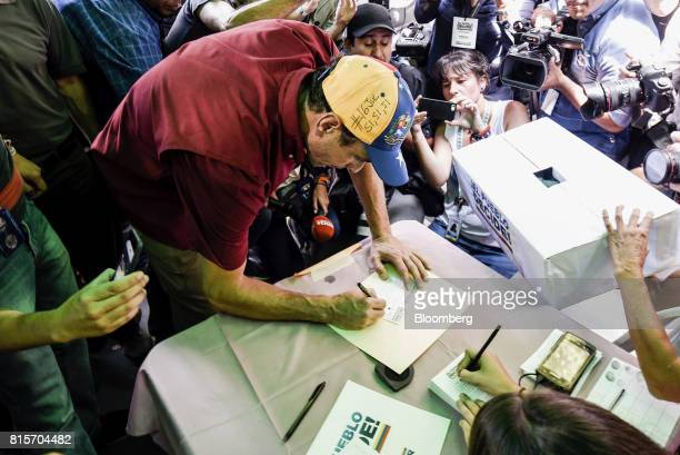 Henrique Capriles opposition leader and governor of the State of Miranda writes on a ballot at a polling station during a symbolic Venezuelan...