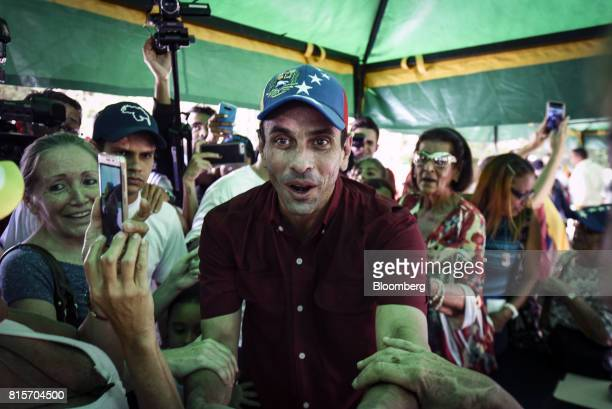 Henrique Capriles opposition leader and governor of the State of Miranda greets voters as he arrives at a polling station to vote during a symbolic...