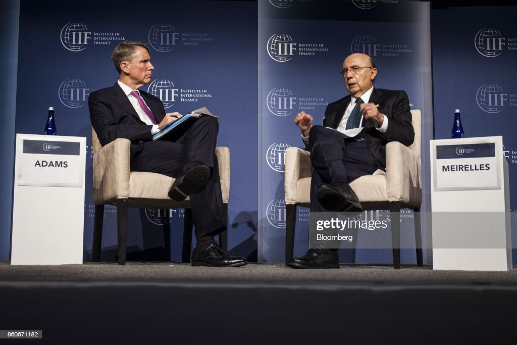 Henrique Meirelles, Brazil's minister of finance, right, speaks while Tim Adams, president and chief executive officer of the Institute of International Finance (IIF), listens during the IIF annual membership meeting in Washington, D.C., U.S., on Thursday, Oct. 12, 2017. Meirelles said that thousands of Venezuelans have crossed the border into Brazil and that some Venezuelans only cross the border to buy food. Photographer: Zach Gibson/Bloomberg via Getty Images