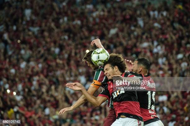 Henrique of Fluminense vies for the ball with Willian Arao and Rever of Flamengo during their Copa Carioca final football match at Maracana stadium...
