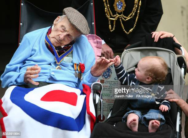 Henry Allingham greets 11monthold Floyd Kearns as he leaves Brighton Town Hall in Brighton East Sussex after being made an Honoury Freeman of the...