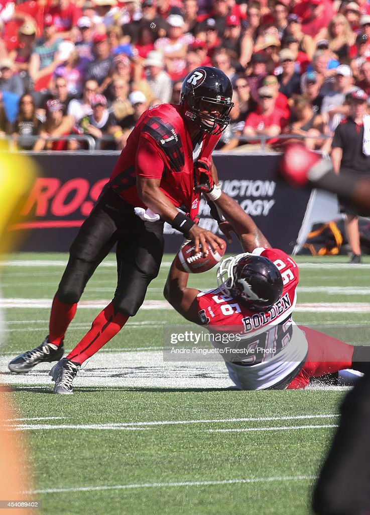 Henry Burris #1 of the Ottawa Redblacks gets hauled down by defensive lineman Demonte' Bolden #96 of the Calgary Stampeders during a CFL game at TD Place Stadium on August 24, 2014 in Ottawa, Ontario, Canada.